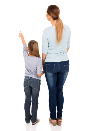 Foto de rear view of young mother and daughter pointing at empty space - Imagen libre de derechos