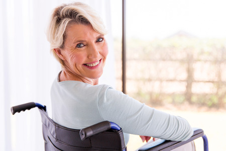 Photo pour happy disabled woman in wheelchair looking back - image libre de droit