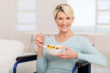 Photo pour portrait of cute mature woman in wheelchair eating fruit salad - image libre de droit