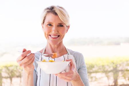 Photo pour happy middle aged woman eating salad at home - image libre de droit