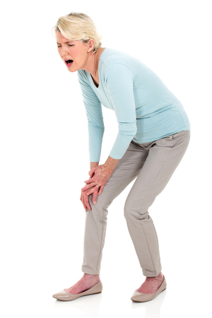 middle aged woman with knee pain isolated on whiteの写真素材