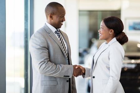 cheerful african car dealer handshake with customer in showroom