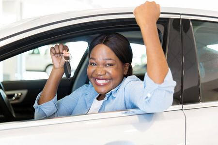 Photo pour cheerful young african woman showing her new car key at dealership - image libre de droit