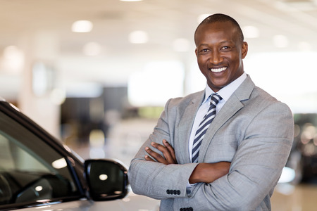 Photo pour african american car dealership principal standing in vehicle showroom - image libre de droit