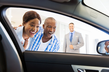 happy african couple choosing luxury car at vehicle dealership looking at the interiorの写真素材