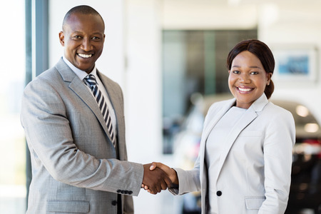 beautiful african woman handshaking with car dealerの写真素材
