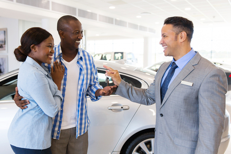 mid age car salesman handing over new car key to african couple in car showroomの写真素材