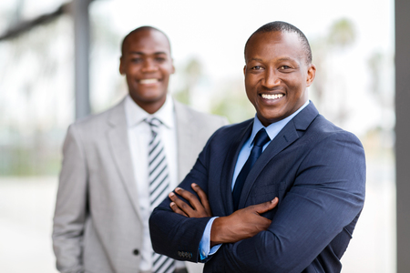 Photo pour cheerful african businessman standing in front of colleague - image libre de droit
