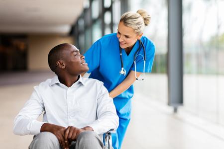 Photo pour caring female nurse talking to disabled patient in hospital - image libre de droit