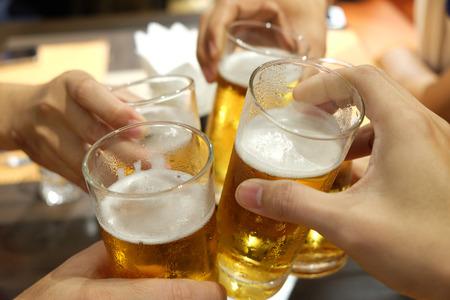 Foto de People having celebration by toasting beer in the glass - Imagen libre de derechos