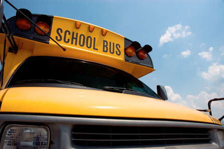 Close-up of the front of a school bus with a blue sky background.