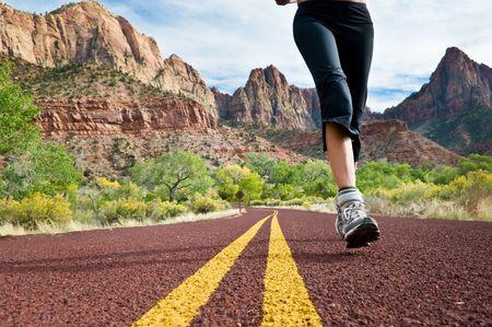Photo pour A woman running down a mountainous road. - image libre de droit