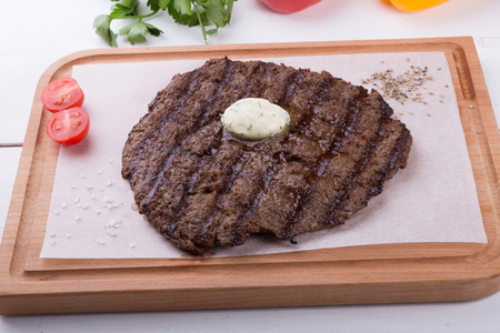 Prepared steak served with butter on wooden board