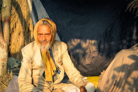 Shantiniketan, West Bengal - circa January 2012: Older man with yellow headcloth on his head wears suit at Baul music festival near Shantiniketan, West Bengal. Documentary editorial.
