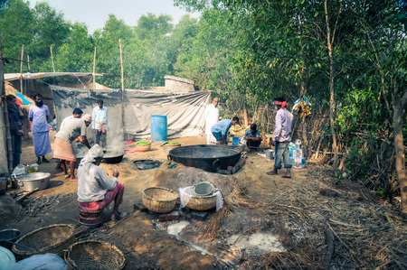 Shantiniketan, West Bengal - circa January 2012: Native women and men prepare meal during Baul music festival in Shantiniketan, West Bengal. Documentary editorial.