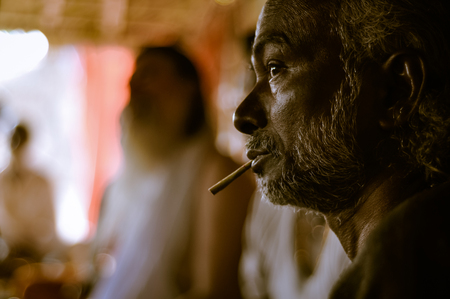 Shantiniketan, West Bengal - circa January 2012: Man smokes cigarette and looks to left at Baul music festival near Shantiniketan, West Bengal. Documentary editorial.