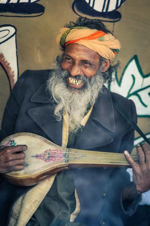 Shantiniketan, West Bengal - circa January 2012: Smiling man with long grey beard plays musical instrument at Baul music festival near Shantiniketan, West Bengal. Documentary editorial.