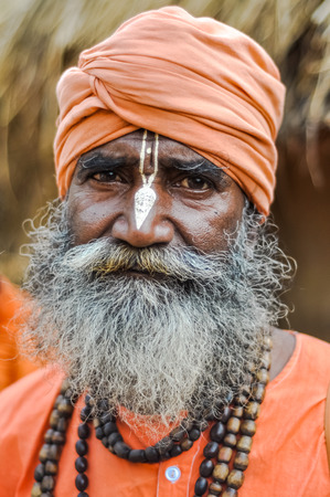 Shantiniketan, West Bengal - circa January 2012: Older man with orange turban has white symbol on forehead and nose during Baul music festival near Shantiniketan, West Bengal. Documentary editorial.