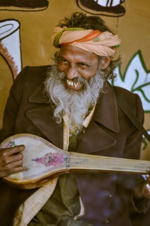 Shantiniketan, West Bengal - circa January 2012: Man with long grey beard plays musical instrument at Baul music festival near Shantiniketan, West Bengal. Documentary editorial.