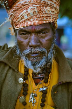 Shantiniketan, West Bengal - circa January 2012: Man with headcloth and grey beard wears string of beads during Baul music festival near Shantiniketan, West Bengal. Documentary editorial.