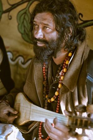Shantiniketan, West Bengal - circa January 2012: Man with longer black hair and beard plays musical instrument at Baul music festival near Shantiniketan, West Bengal. Documentary editorial.