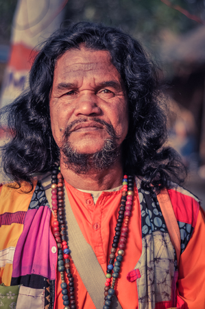 Shantiniketan, West Bengal - circa January 2012: Man with long black hair wears colourful clothes at Baul music festival near Shantiniketan, West Bengal. Documentary editorial.