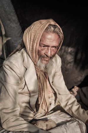 Shantiniketan, West Bengal - circa January 2012: Older man with grey beard and yellow headcloth on his head wears suit at Baul music festival near Shantiniketan, West Bengal. Documentary editorial.