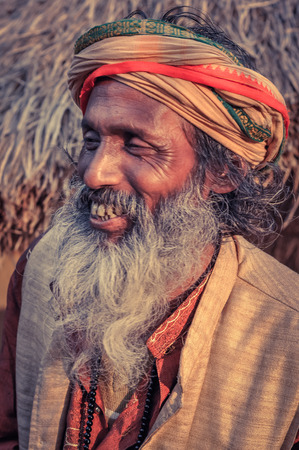 Shantiniketan, West Bengal - circa January 2012: Older man with colourful turban and long grey beard smiles at Baul music festival near Shantiniketan, West Bengal. Documentary editorial.