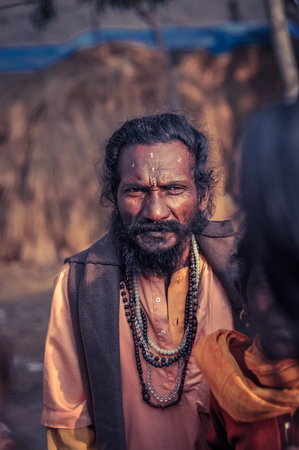 Shantiniketan, West Bengal - circa January 2012: Man with black hair and beard has symbol on his forehead and wears string of beads at Baul music festival, West Bengal. Documentary editorial.