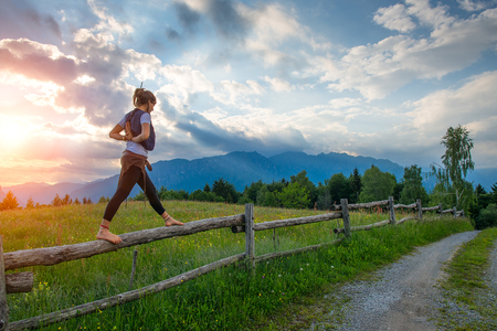 Foto de Casual girl relaxes doing stretching and yoga alone in the mountains over a fence in a beautiful spring meadow. - Imagen libre de derechos