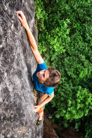 Girl climbing on the rock safely roped