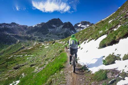 Foto de Mountain biking in a small narrow mountain path - Imagen libre de derechos