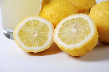 lemons and lemon juice on a white background