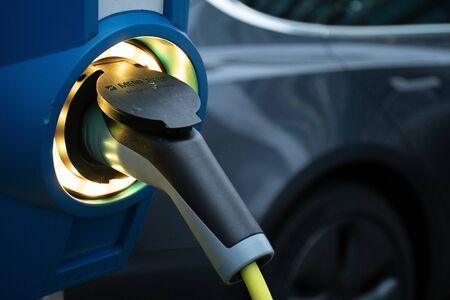 Photo pour Electric vehicle charging station, EV charging station, electric recharging point, charging point, charge point, electronic charging station ECS with car on background - image libre de droit