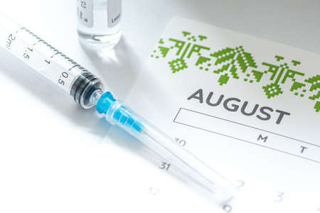 Photo pour Syringe, vial and calendar with month of August on a white table ready to be used. Covid or Coronavirus vaccine background - image libre de droit