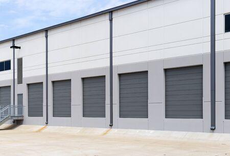 Photo for Empty warehouse loading dock white walls gray metal sliding doors - Royalty Free Image
