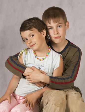 Brother hug a Sister Sitting On Couch
