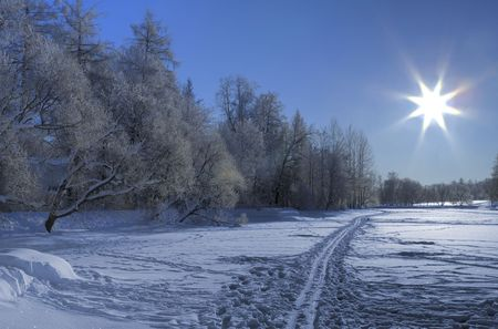 Snow ski road on a frozen lake and Sun backlight. North of Russia