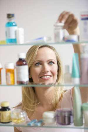 A young woman reaches for a container in her medicine cabinet.  Vertical shot.