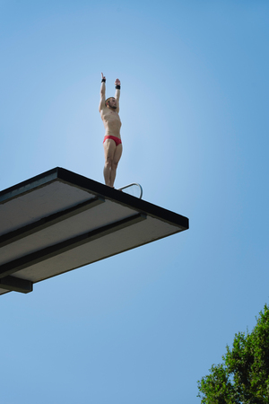 Male diver, preparing to dive from 10 meter high diving platform