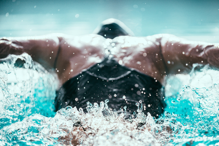 Photo pour Butterfly stroke swimmer from behind - image libre de droit