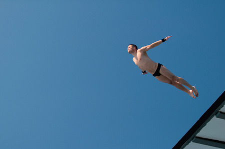 Photo pour Professional diver caught in flight during attractive old style dive from 10 meter high platform. - image libre de droit