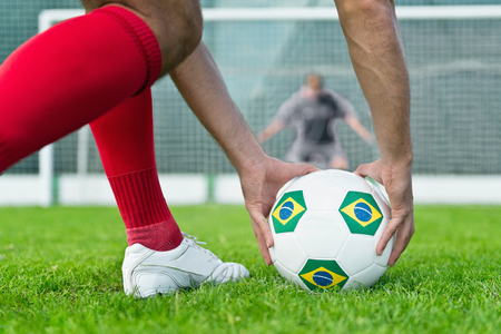 Soccer player placing Brazilian ball on penalty kick spot
