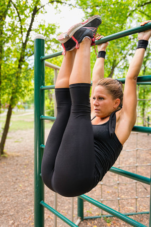 Young woman exercising on stall bars in park