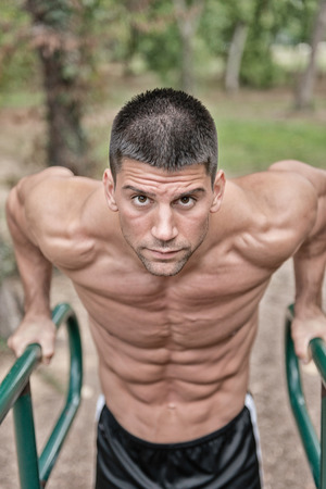 Muscular male athlete exercising on parallel bars in park