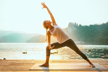 Foto de Beautiful woman practicing Yoga by the lake - Sun salutation series - Extended triangle pose - Water birds - Toned image - Imagen libre de derechos