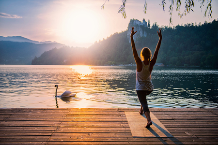 Foto per Beautiful woman practicing Yoga by the lake - Sun salutation series - Swan passing by - Toned image - Immagine Royalty Free