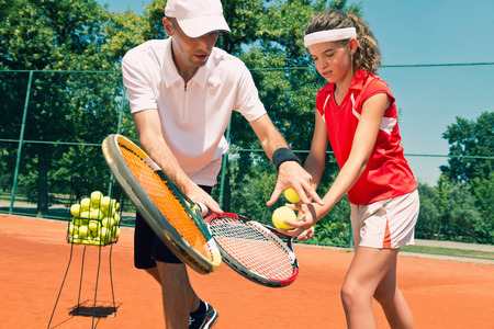 Tennis lesson - instructor working with teenager. Toned image