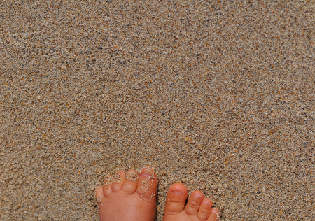 Baby feet in the sand. Lots of copy space available