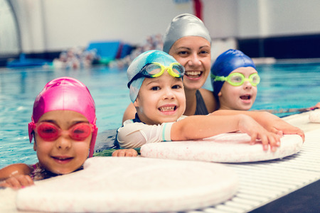 Photo pour Kids with swimming instructor, having fun on the pool edge - image libre de droit